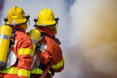 Spruzzo d'acqua di due pompieri dai wi ad alta pressione di bordi dell'ugello Fotografia Stock Libera da Diritti