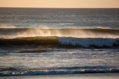 Spruzzo dell'oceano dalle onde al tramonto fotografia stock