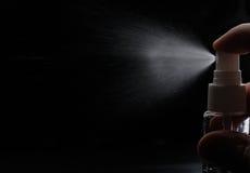 Spruzzo di profumo sul nero fotografie stock