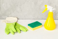 Spruzzo, spugna e guanti della finestra su fondo grigio, concetto di pulizie di primavera Detersivi ed accessori di pulizia Picco fotografia stock libera da diritti