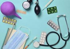 Sprzęt medyczny na błękitnym tle Enema, bąbel pigułki, notepad, stetoskop, strzykawka, termometr, manometr Medyczny conc obraz stock