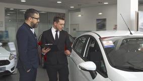 Sprzedaż kierownika explaines kontrakt klient przy przedstawicielstwem firmy samochodowej zdjęcia stock