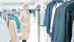 Sprzedaż, moda, konsumeryzm i ludzie pojęć, - kobiet torba na zakupy wybierać odziewa w centrum handlowym lub sklepie odzieżowym zbiory wideo