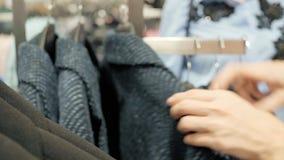 Sprzedaż, moda, konsumeryzm i ludzie pojęć, - kobiet torba na zakupy wybierać odziewa w centrum handlowym lub sklepie odzieżowym zdjęcie wideo
