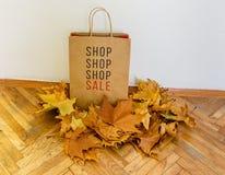Sprzedaż znak na torba na zakupy otaczającym z żółtymi liśćmi Zdjęcie Stock