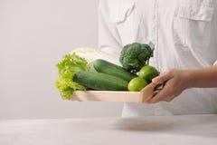 sprzedażny Zdrowy weganinu jedzenie Świezi warzywa, jagody, zielenie i owoc w drewnianej tacy w mężczyzna rękach, fotografia royalty free