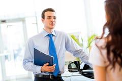 Sprzedaż kierownik przy sala wystawowa samochodem Obraz Stock