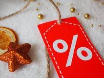 Sprzedaży zima, boże narodzenie pomarańcze gwiazda z dyskontową etykietką na świątecznym tle obrazy royalty free