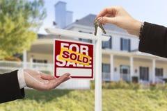 Sprzedający znak i agent Wręcza Nad kluczami Nowy dom Zdjęcie Stock