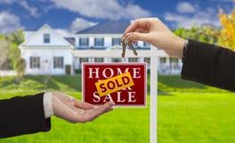 Sprzedający znak i agent Wręcza Nad kluczami Nowy dom Fotografia Royalty Free