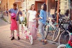 Sprzedawanie bicykl - rodzina z szczęśliwym dzieciakiem ma zabawa plenerowego zakupy nowego bicykl i hełmy obraz stock