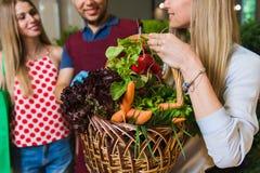 Sprzedawca i dwa dziewczyny z koszem warzywa Fotografia Stock