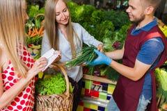 Sprzedawca i dwa dziewczyny z koszem warzywa Zdjęcie Royalty Free