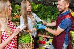 Sprzedawca i dwa dziewczyny z koszem warzywa Obraz Stock