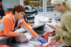 Sprzedawca i nabywca w masarka sklepie obraz stock