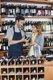 Sprzedawca Pokazuje wino butelkę klient Obraz Stock