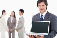Sprzedawca pokazywać laptopu ekran z kolegami Fotografia Stock