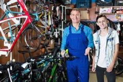 Sprzedawca pomaga chłopiec wybiera bicykl w sporta sklepie Zdjęcie Royalty Free