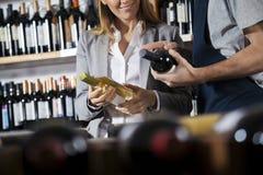 Sprzedawca Pomaga Żeńskiego klienta W Wybierać wino obraz royalty free