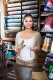 Sprzedawca pomagać przy gotówkowym biurkiem Fotografia Royalty Free