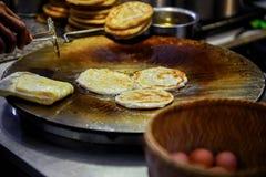 Sprzedawca ręka smaży wokoło roti ciasta w gorącej niecce zdjęcie stock