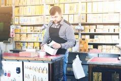 Sprzedawca sortuje pudełka z drzwi szczegółami w sklepie Fotografia Royalty Free