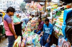 Sprzedawca sprzedaje plastikowe rzeczy w ulicznym rynku obraz royalty free