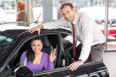 Sprzedawca sprzedaje samochód szczęśliwy klient zdjęcia royalty free