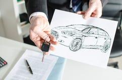 Sprzedawca trzyma klucz i pokazuje samochodowego projekt Zdjęcia Stock