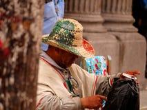 Sprzedawca Uliczny Jest ubranym kapelusz w Meksykańskiej flagi kolorach z oczami Zaciemniającymi kapeluszem obrazy stock