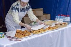 Sprzedawca w fartuchu w handlowym namiocie Kaukaski pojawienie kobieta sprzedaje babeczki i kulebiaki obrazy royalty free
