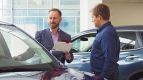 Sprzedawca w kostiumu pokazuje klientowi samochodowego wnętrze fotografia stock