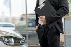 Sprzedawca z schowkiem stoi obok samochodu Obraz Stock