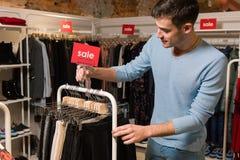 Sprzedawca z sprzedaży czerwonym nameplate w ubrania sklepie fotografia stock