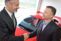 Sprzedawcy chwiania ręki z klientem po sprzedawać on samochodowy Obraz Royalty Free