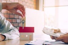 Sprzedawcy domu maklery zapewniają klucz nowi właściciele domu g i nabywcy Obrazy Stock