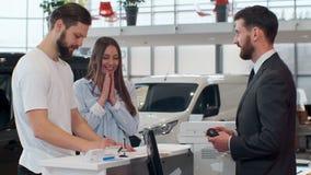 Sprzedawcy podpisywania kontrakt, daje pi?ru m??czyzna M?ody faceta k?adzenia podpis na dokumencie Sprzedawca daje kluczom samoch zdjęcie wideo