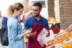 Sprzedawcy pomaga klient wybierać niektóre typ owoc w zdrowie sklepu spożywczego sklepie zdjęcia royalty free