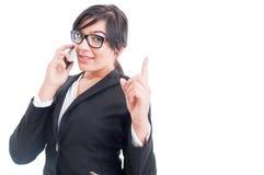 Sprzedawczyni opowiada na telefonie i robi czekanie gestowi Zdjęcia Royalty Free