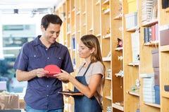 Sprzedawczyni Pokazuje kartka z pozdrowieniami klient zdjęcia stock