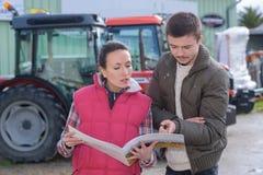 Sprzedawczyni próba sprzedawać nowego ciągnika rolnik Obraz Stock