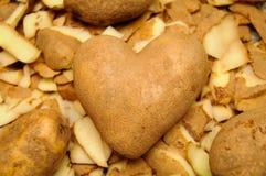 Spud of Hearts. A heart of potato amid potato peels royalty free stock image