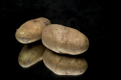 Spud potatoes on reflective surface. Two potatoes on a black reflective surface royalty free stock images