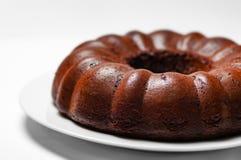 Spugna del dolce di parte concavo del cioccolato intera su un primo piano bianco del fondo del piatto Immagine Stock Libera da Diritti