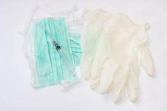 Spuit en naald op chirurgische masker en handschoenen Stock Afbeelding