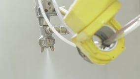 Spuitpistool met verf in geautomatiseerde productie actie Close-up automatisch met de nevel die van de robothand met het schilder stock video
