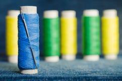 Spule des blauen Fadens mit einer Nadel auf dem Hintergrund von Spulen von grünen und gelben Faden auf einem Denimgewebe stockfotografie