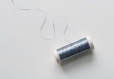 Spule des blauen metallischen Threads Stockfotos