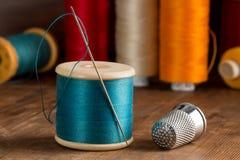 Spule des blauen Threads, der Nadel und der Muffe Stockbild