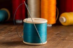 Spule des blauen Threads und der Nadel Stockfotografie